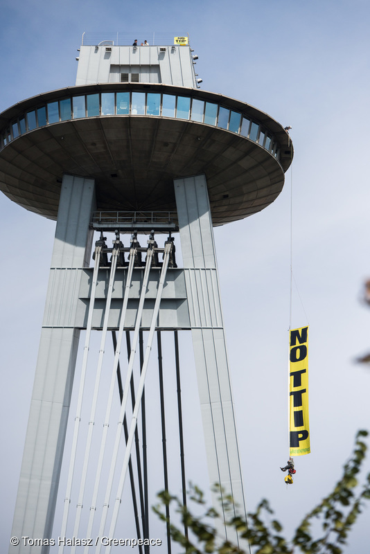 """Ten climbers from Austria, Slovakia and Croatia scale Bratislava's UFO tower over the Danube to display a banner reading """"NO TTIP"""", as ministers meet in the city below to decide the fate of EU trade deals with the US and Canada."""